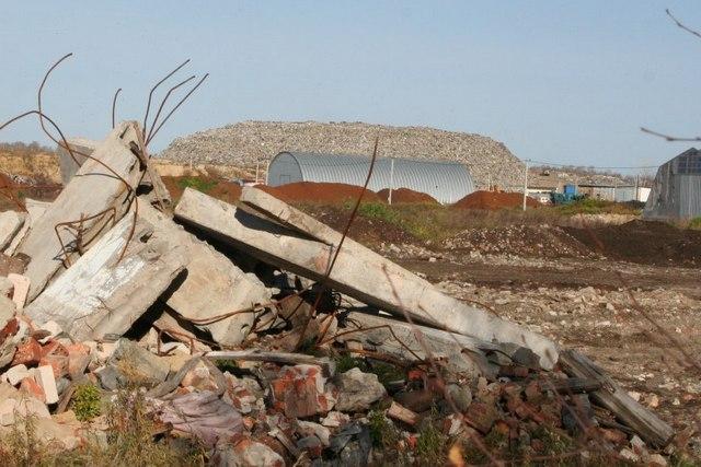 На прилегающей к полигону частной территории утилизуется строительный мусор. На заднем плане видна свалка мусора высотой 20 метров