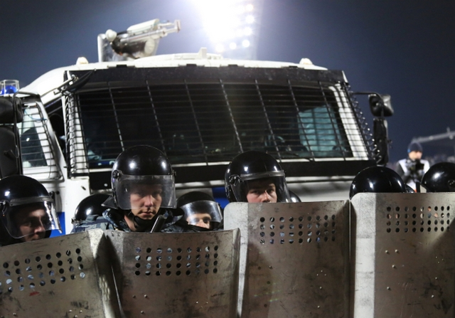 ОМОН защищает поле от фанатов Спартака на матче 1/16 финала Кубка России
