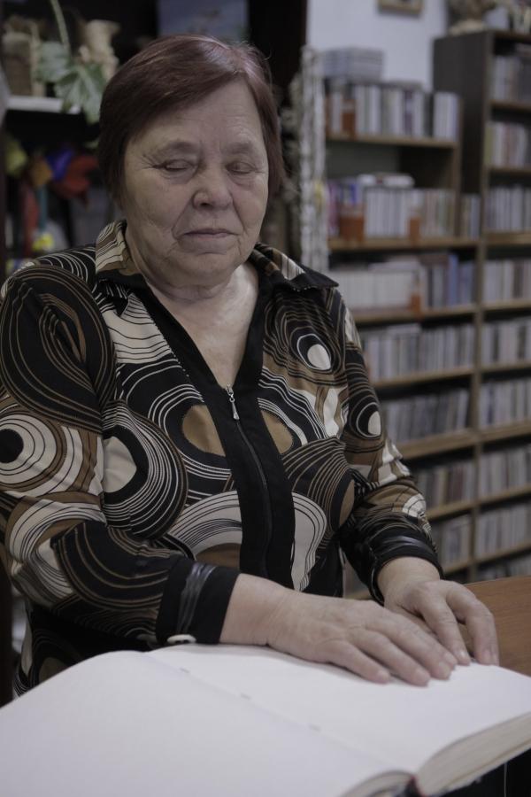 Вера Прокофьевна читает книги, написанные шрифтом Брайля