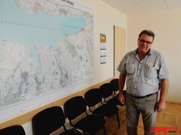 Владимир показывает на карте водохранилища реконструированную дамбу