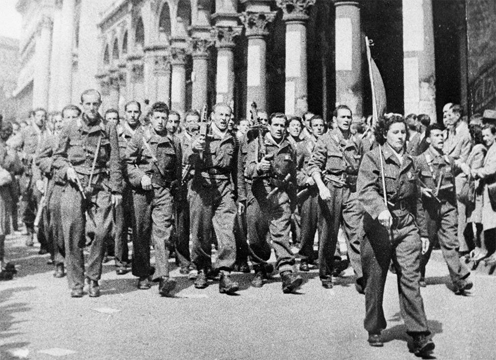 Вооруженный отряд движения Сопротивления шагает по улицам Милана во время Второй Мировой войны. 1945 год.