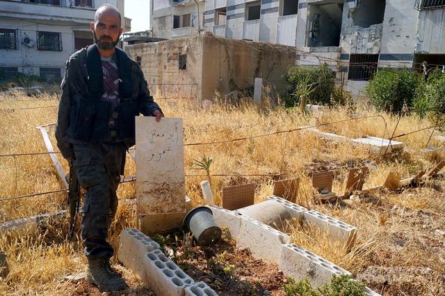 Офицер сирийской армии показывает кладбище боевиков, устроенное ими в городском скверике
