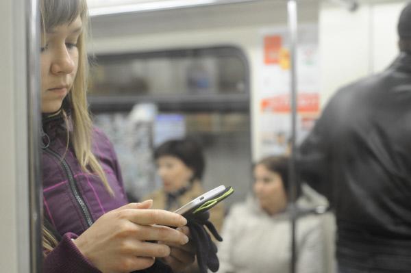 Пассажирка пользуется планшетным компьютером на одной из станций Московского метрополитена