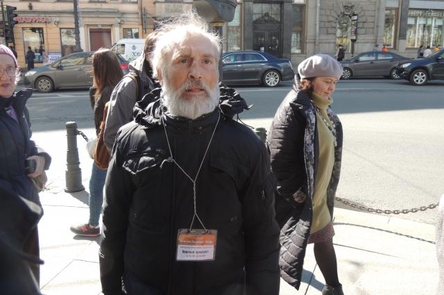 Вячеслав Романович рассказывает туристам историю домов на Невском проспекте.