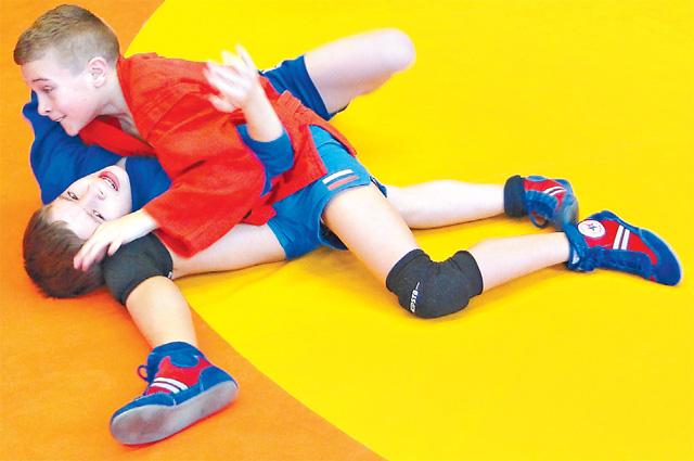 Участники спортивного клуба «Алкид» учат элементы техники и тактики борьбы самбо.
