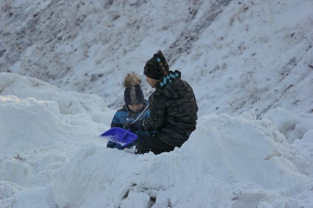 Дети любят играть в сугробах зимой.
