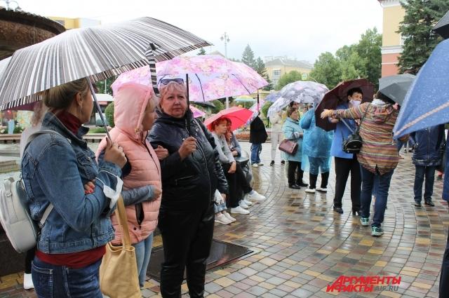 Зрители прятались под зонтами, но не уходили.