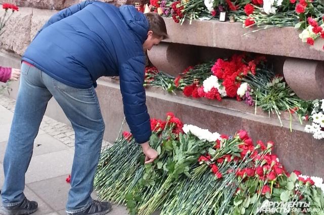 Петербуржцы несут цветы к метро