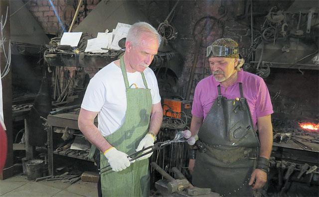 Александр Романов и губернатор Сергей Морозов за изготовлением кованых вишен для дерева памяти.