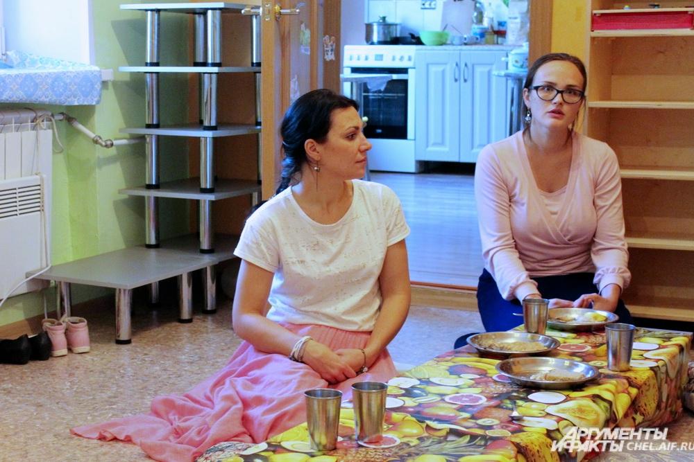 Воспитатели вместе с детьми завтракают за нижким столиком, сидя на подушках.