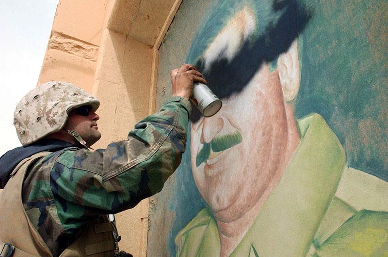 Солдат армии США закрашивает портрет Саддама Хусейна в Ираке