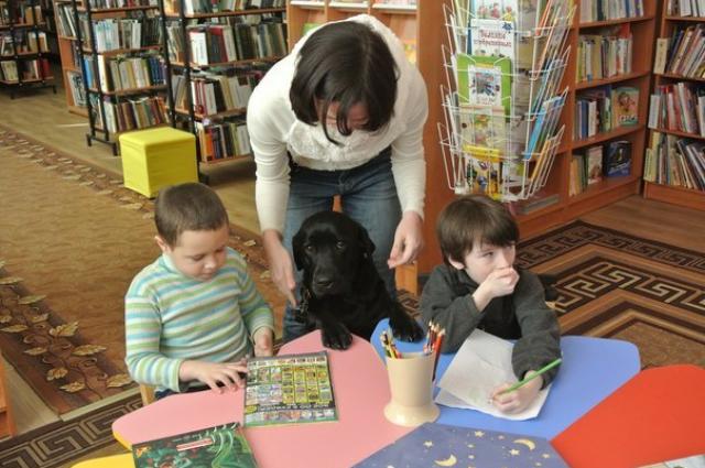 Лабрадор Лейла с удовольствием слушает, как читают дети.