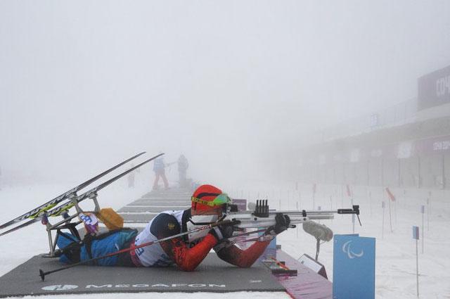 Роман Петушков на огневом рубеже на средней дистанции в классе LW 10-12 (сидя) среди мужчин в соревнованиях по биатлону на XI Паралимпийских зимних играх в Сочи