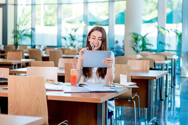 Девушка с планшетным компьютером в школе