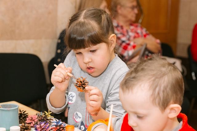 Маленькая Оля Попова раскрашивает шишки на празднике.