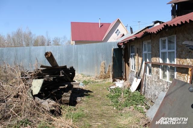 На участке Власова много хлама. За забором — соседи, которые, как он утверждает, претендуют на его дом.
