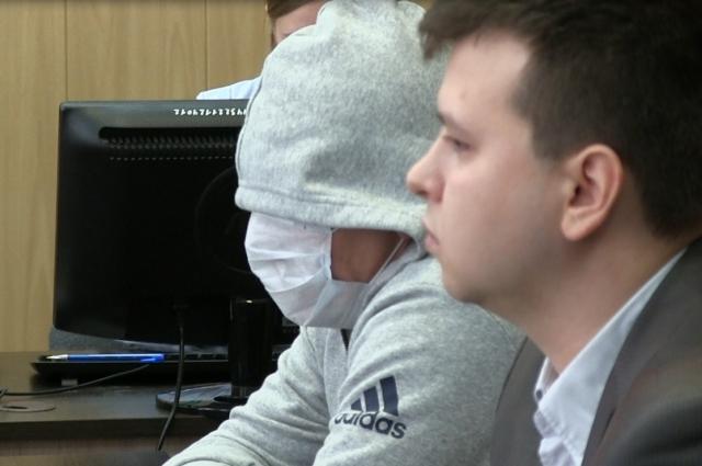 Отец подозреваемого во время судебного заседания закрывал лицо медицинской маской и не снимал шапку.