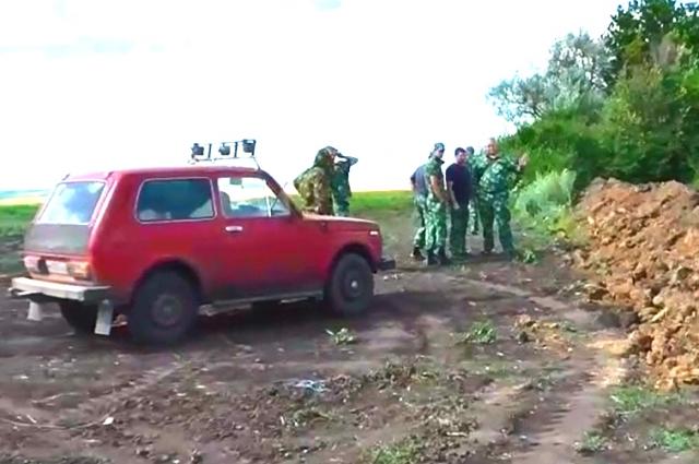 Мужчины в камуфляжной форме из частного охранного предприятия (ЧОП) не пускали на поля колхозников.