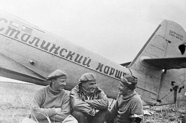 Лётчики Валерий Чкалов (в центре), Георгий Байдуков (слева) и Александр Беляков сидят около самолёта после приземления на острове Удд (в последствии остров Чкалова) в Охотском море из-за штормовой погоды во время беспосадочного перелёта Москва – Дальний Восток.