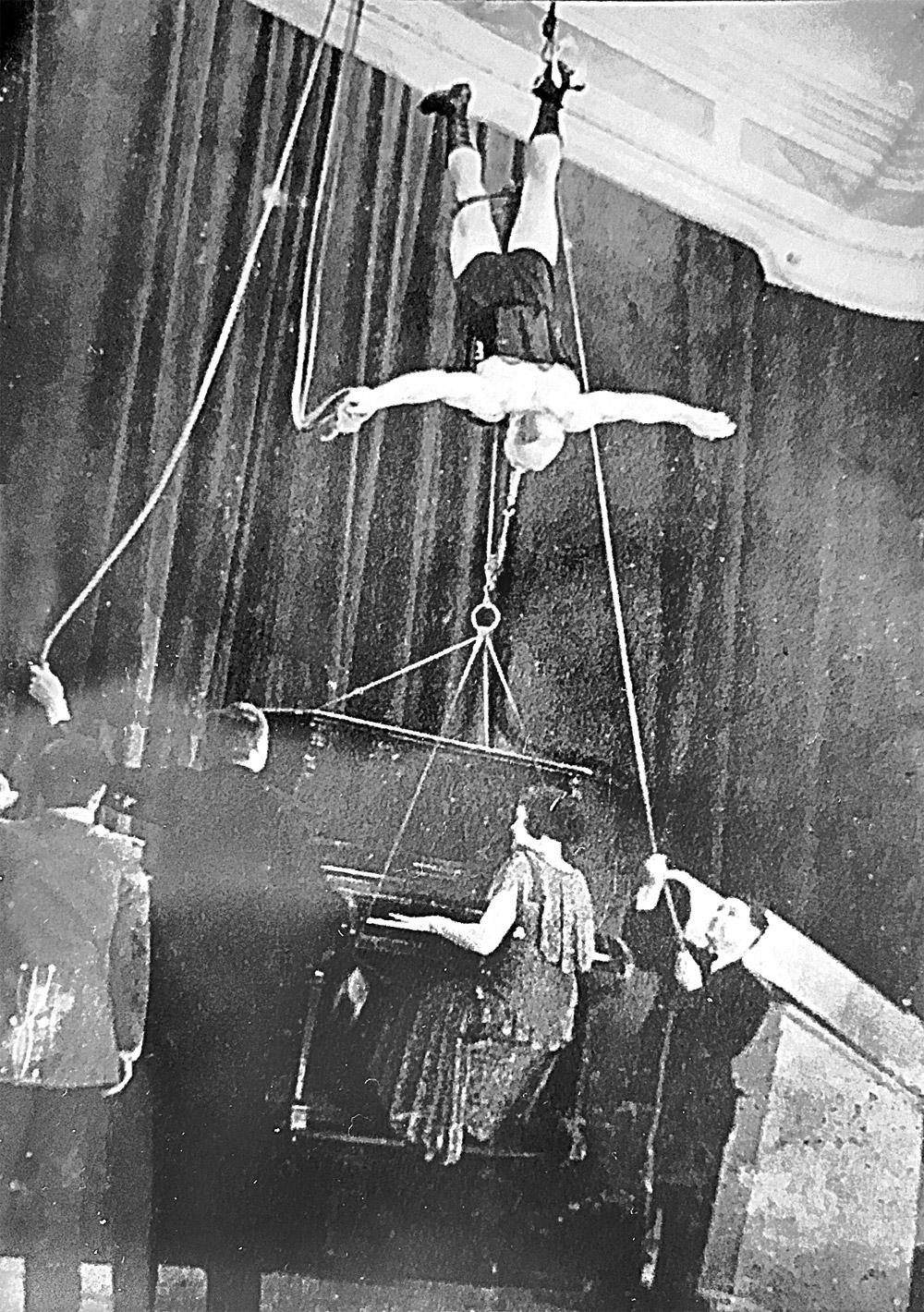 Силача поднимают под купол цирка, в то вре- мя как он держит зубами канат, на котором висит рояль с играющей на нём акробаткой.