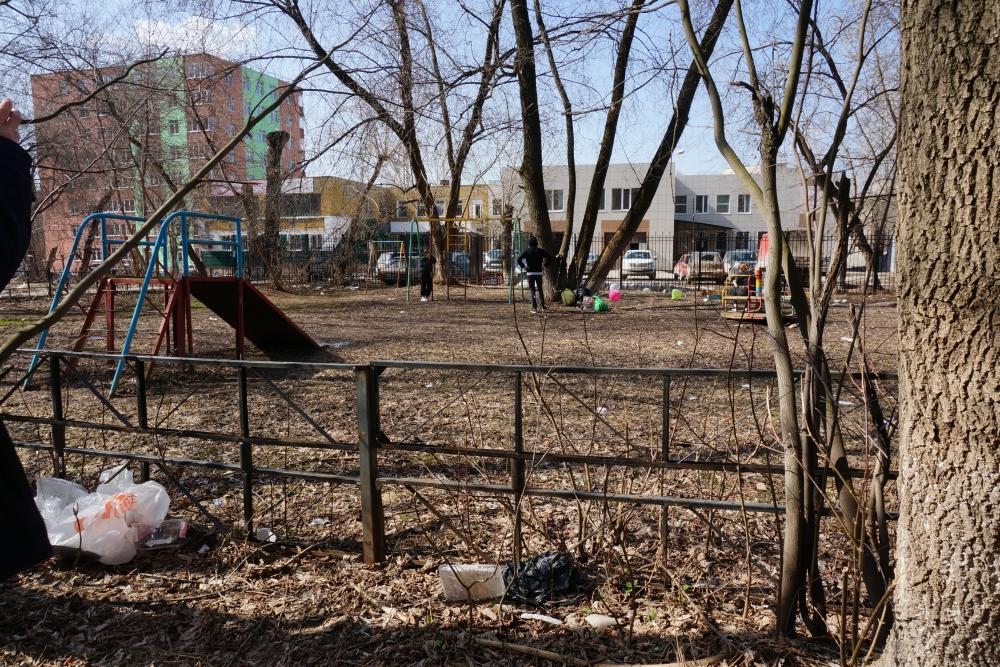 Дети играют на площадке, на которой лежит мусор.