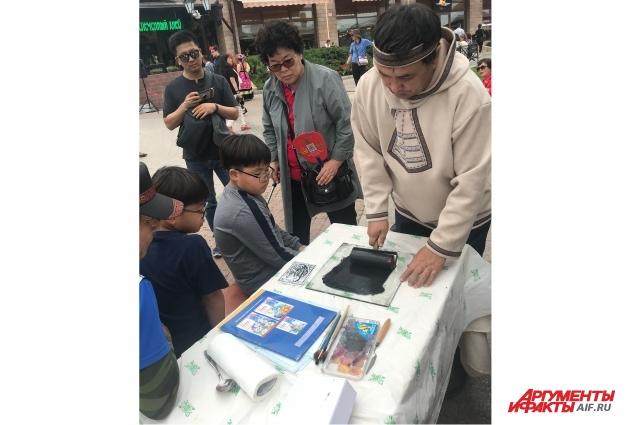 Туристы из Китая учились делать гравюры с сюжетами из жизни коренных народов Сибири.