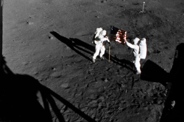 Нил Армстронг (слева) и Эдвин Олдрин устанавливают на Луне флаг США.