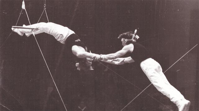 Павел Беляевский (слева на фото) ловит партнёра в своём коронном номере «Полёт с батутом». Трюк был настолько опасным, что его запретили исполнять в цирках.
