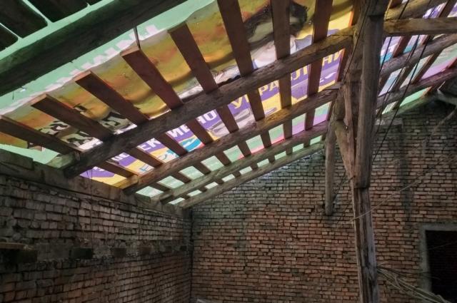 Строители затянули крышу баннером и прекратили ремонтные работы.