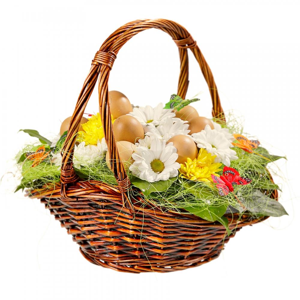 Украшенная цветами корзинка с пасхальными яйцами - идеальное украшение праздничного стола.