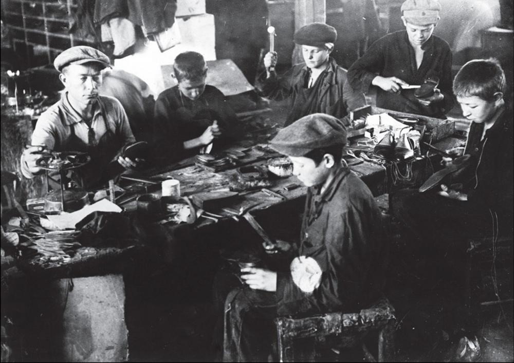 Бывшие беспризорные учатся сапожному делу в специально открытых мастерских Помощь, г. Николаев, 1931 год.