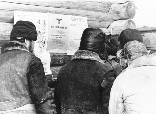Крестьяне в русской деревне читают немецкие аграрные постановления.