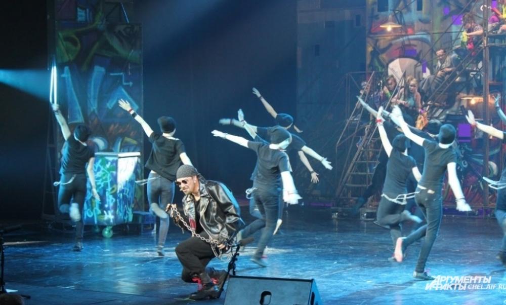В спектакле диалоги персонажей чередовались с песнями-монологами и массовыми танцевальными номерами.