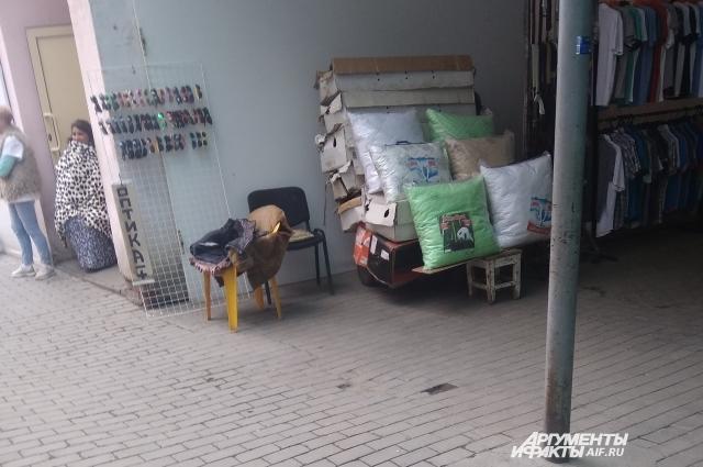 Замерзнув, продавец постельных принадлежностей накинула плед и спряталась за угол.