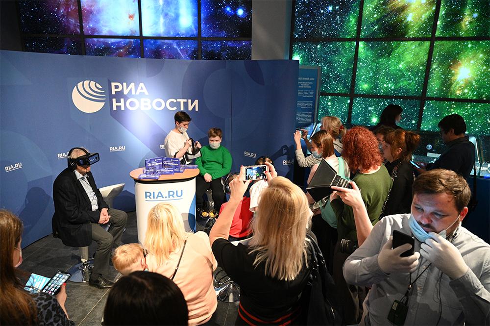 Посетители настенде РИА «Новости» вовремя презентации VR-проектов RIA Lab врамках Недели Космонавтики вМосковском планетарии.
