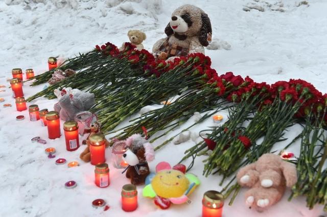 Люди выложили цветы, свечи и игрушки на снегу.