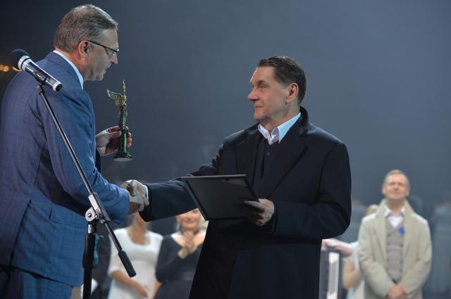 Врио губернатора Омской области Александр Бурков вручает памятный знак.