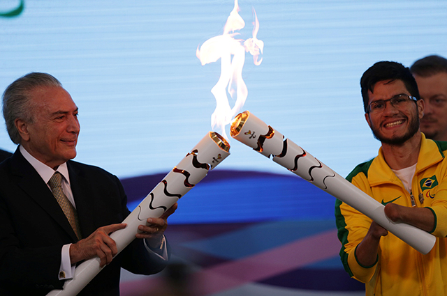 И.О. обязанности президента Бразилии Мишел Темер )слева) зажигает огонь Паралимпиады.