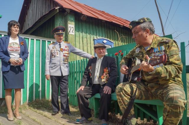 В деревне Еловая Емельяновского района участники автопробега устроили импровизированный концерт у ворот дома ветерана.