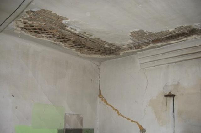Стены квартир в жилом здании опоясали трещины.