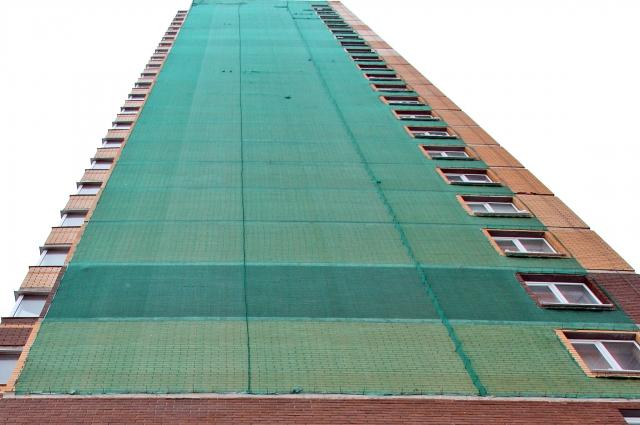 Здания построили лишь несколько лет назад, а фасады уже затянуты аварийной сеткой.