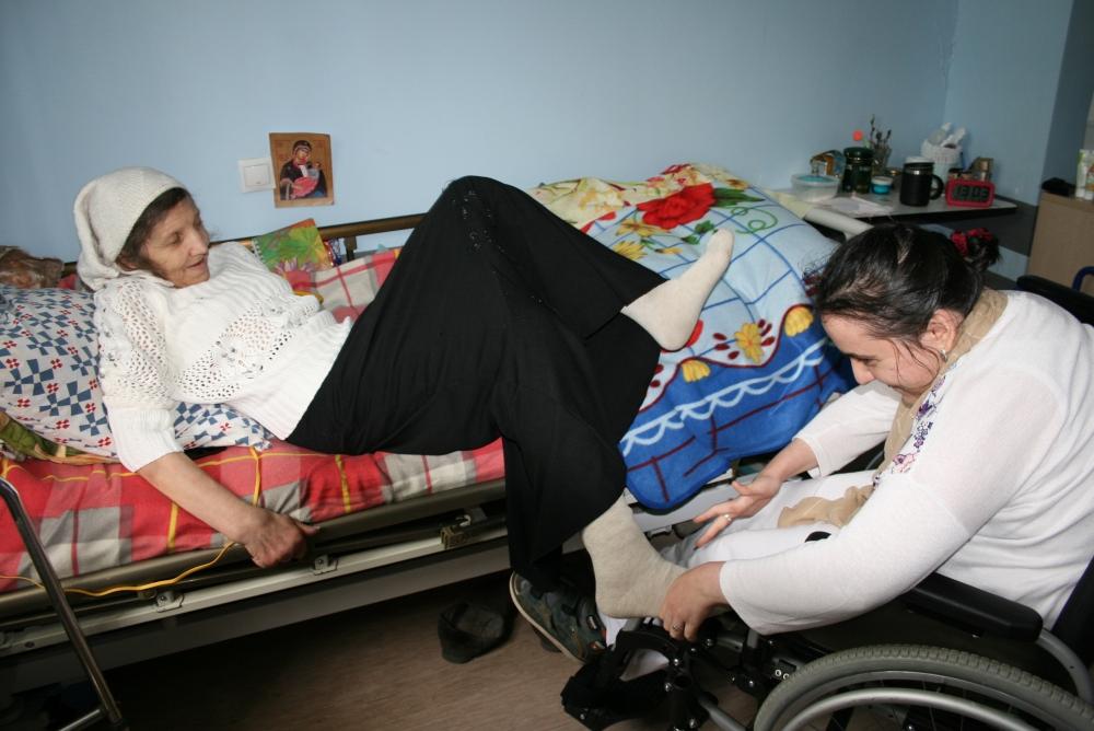 Когда мы заходили в эту комнату, соседка Натальи Ивановны, Лия, подъехав к кровати на коляске, помогала женщине удобнее устроиться.