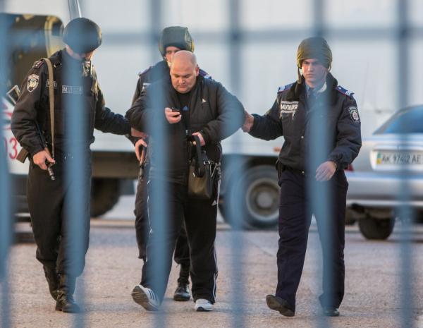 Сотрудники милиции выдворяют неизвестного мужчину с территории фотограмметрического центра украинской армии на улице Кубанской в Симферополе. 18 марта, по некоторым данным, центр пытались захватить неустановленные люди