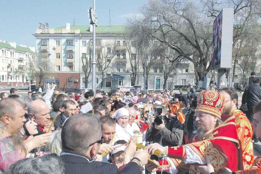 Благодатный огонь раздают верующим во время Пасхальной вечерни на Соборной площади Белгорода.