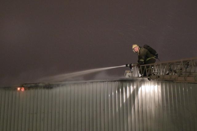 Пожарные проливают водой горевший конструкции.
