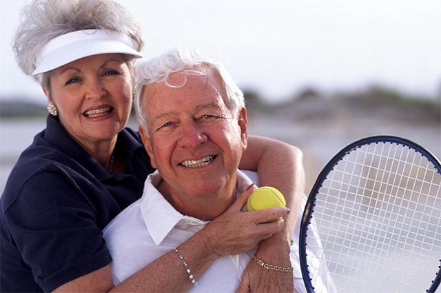 Пожилая пара играет в теннис