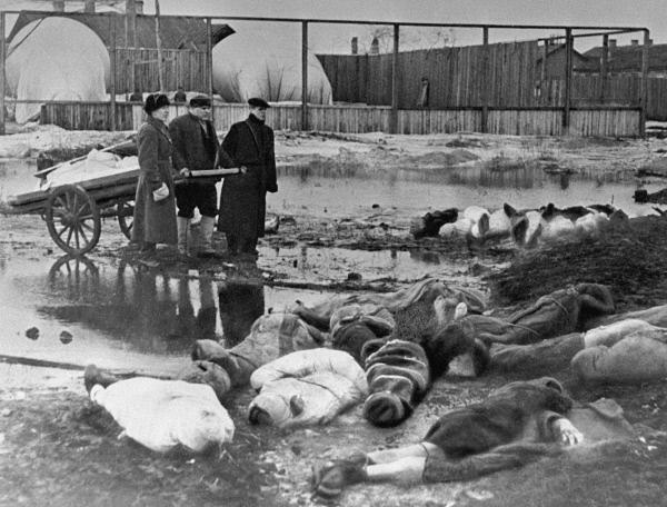 Трое мужчин хоронят умерших в дни блокады в Ленинграде. Волково кладбище