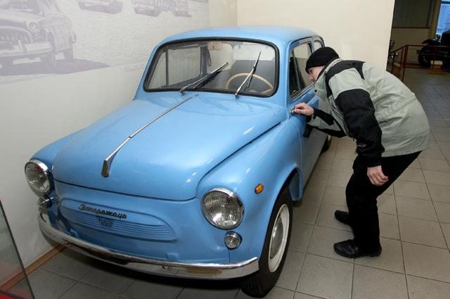 Посетитель у автомобиля ЗАЗ-965 «Запорожец» в экспозиции Музея автомотостарины во Владивостоке.