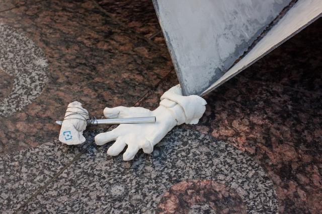 Скульптура представляет собой придавленную самолетиком руку с молотком.