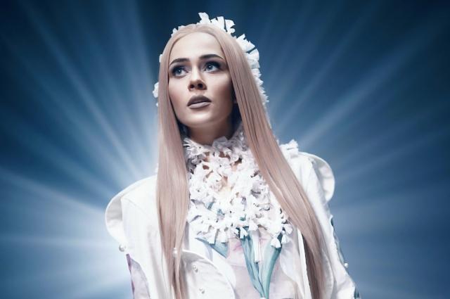 Юлия Санина в клипе одета в белое платье с этномотивами